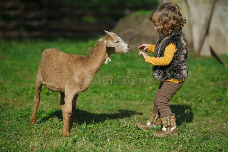 Meisjespelen met geit op het landbouwbedrijf stock fotografie