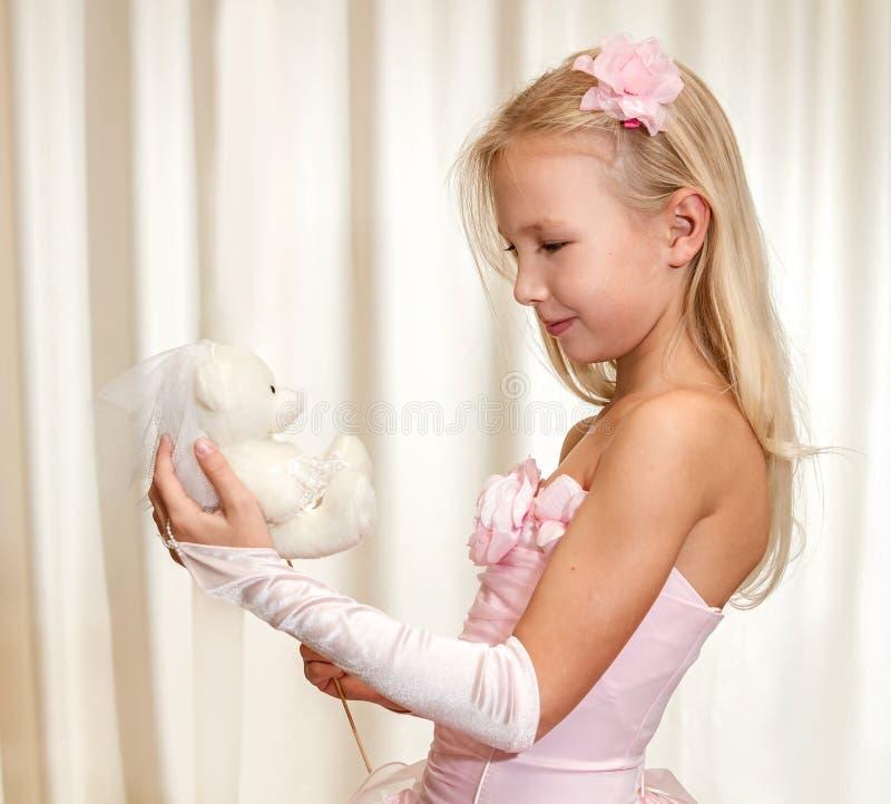 Meisjespelen met huwelijksteddybeer stock afbeelding