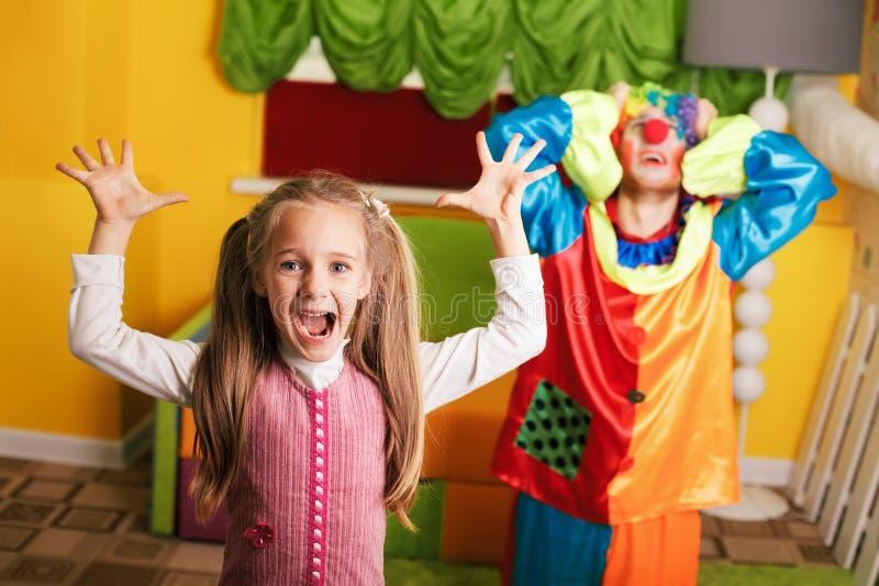 Meisjespelen met verstoorde clown royalty-vrije stock foto