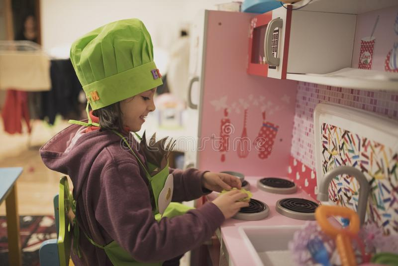 Meisjespelen in stuk speelgoed keuken stock fotografie