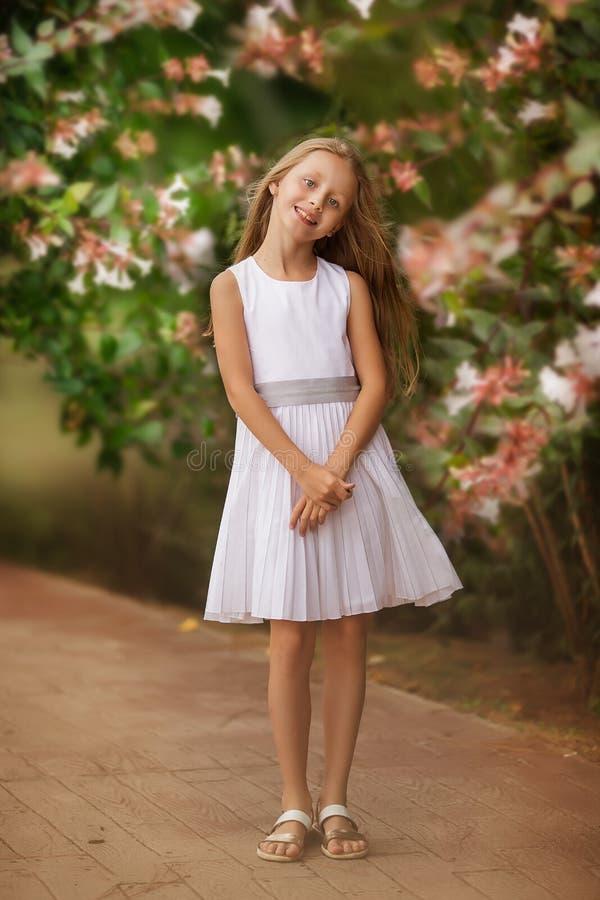 Meisjesportret die in mooie witte kleding zich buiten in park of tuin dichtbij bloemenstruik bevinden royalty-vrije stock afbeeldingen