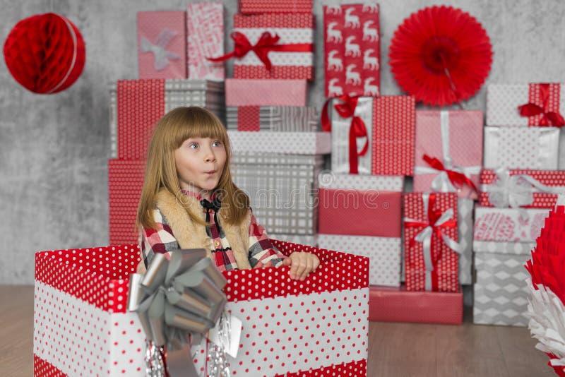 Meisjesprongen omhoog van een grote giftdoos in wit-rode studio royalty-vrije stock foto's