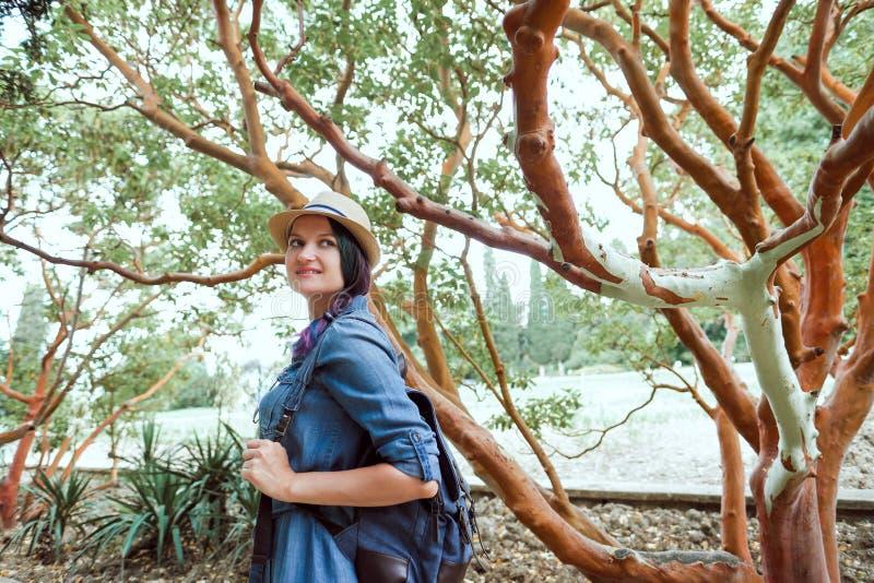 Meisjesreiziger in een park op een achtergrond van takken van boom glimlachen die in een kader kijken stock fotografie