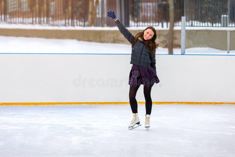 Meisjesschaatser die op ijs in de winter schaatsen stock foto