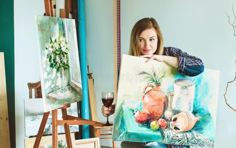 Meisjesschilder met een palet van kleuren en een glas wijn in royalty-vrije stock foto's