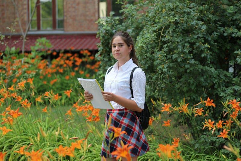 Meisjesschoolmeisje met een omslag in zijn handen stock afbeeldingen