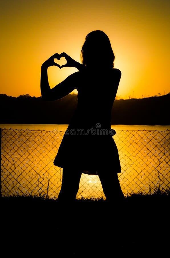 Meisjessilhouet bij zonsondergang stock afbeeldingen
