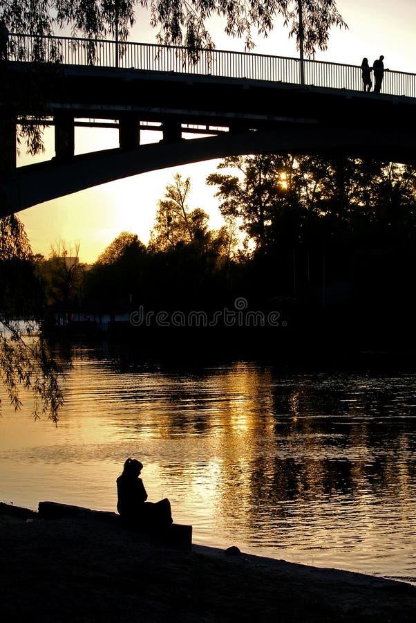 Meisjessilhouet op de zonsondergang dichtbij water royalty-vrije stock afbeelding