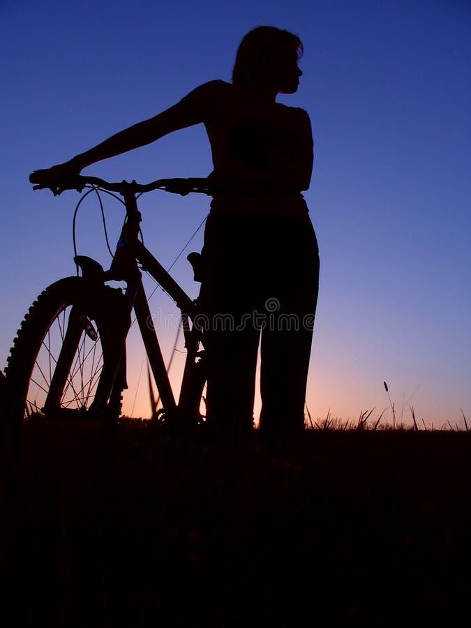 Meisjessilhouet van fietser het berijden stock afbeelding
