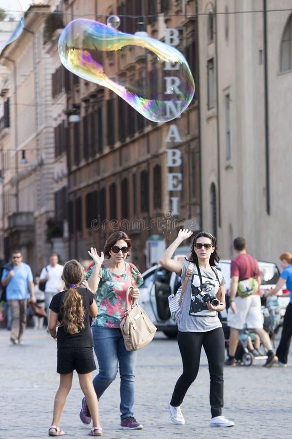 Meisjesspelen met grote zeepbel stock afbeeldingen