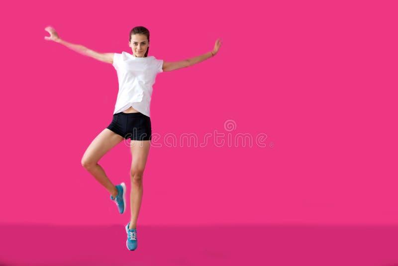 Meisjessportman het stellen op een roze achtergrond royalty-vrije stock foto's