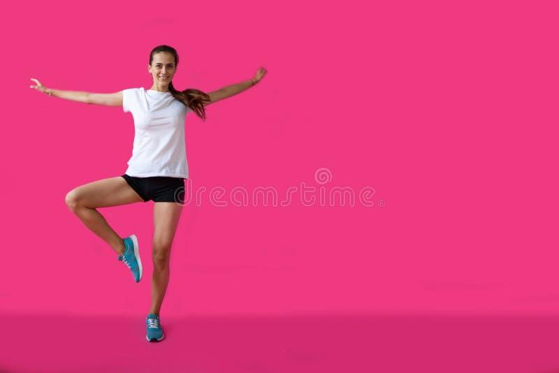 Meisjessportman het stellen op een roze achtergrond royalty-vrije stock afbeelding