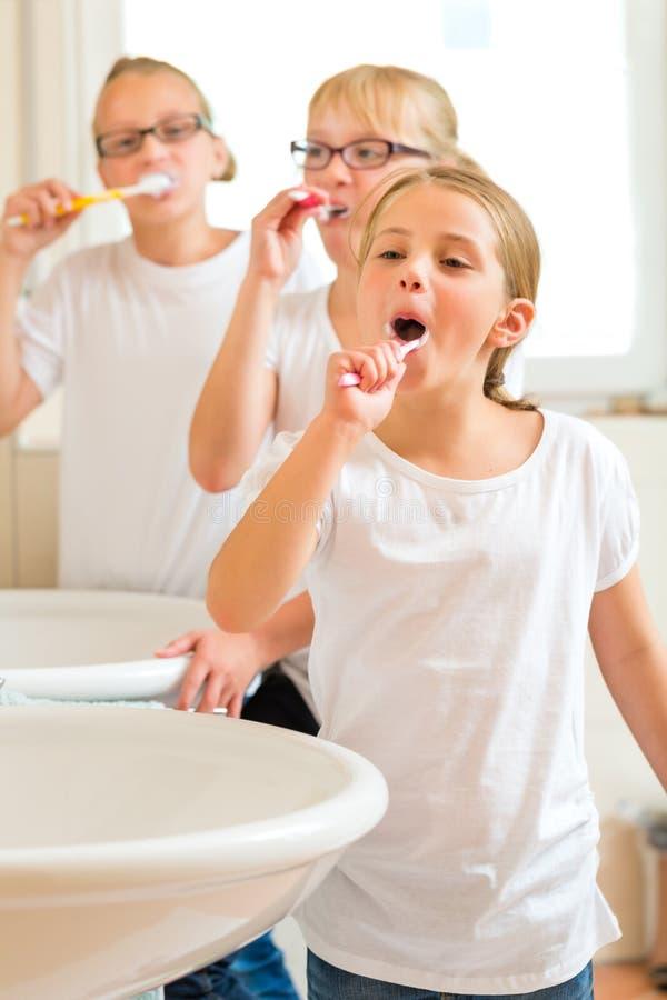 Meisjestand die in de badruimte borstelen stock afbeeldingen