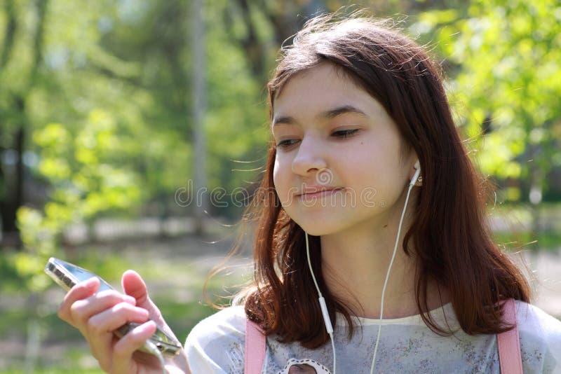 Meisjestiener die aan muziek van een mobiele telefoon luisteren Portret van een meisje in hoofdtelefoonsclose-up Een jong meisje  stock fotografie