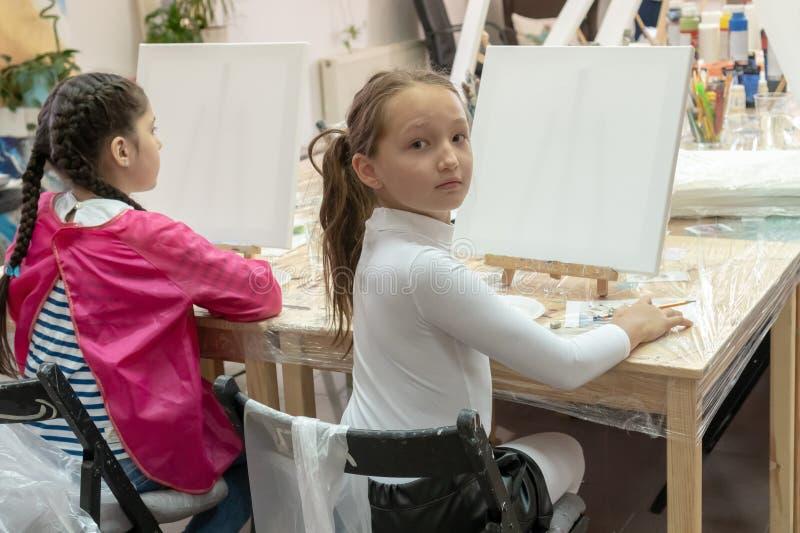 Meisjestiener 9 jaar oude zittings bij een lijst voor de schildersezel en het bekijken de camera Binnenland van de kunstacademie  royalty-vrije stock foto