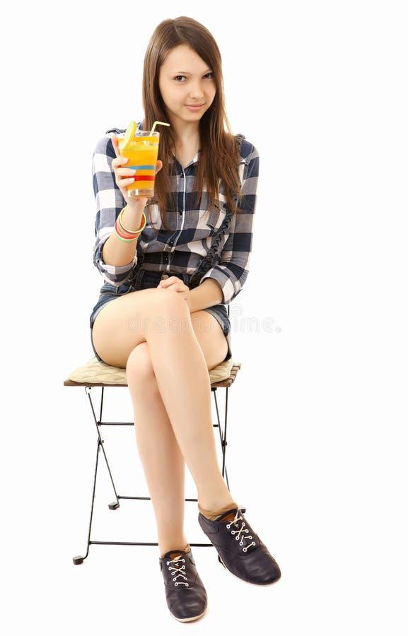 Meisjestiener, Kaukasische verschijning die, brunette, een plaidoverhemd en korte denimborrels dragen, die een glas van drank houd royalty-vrije stock foto