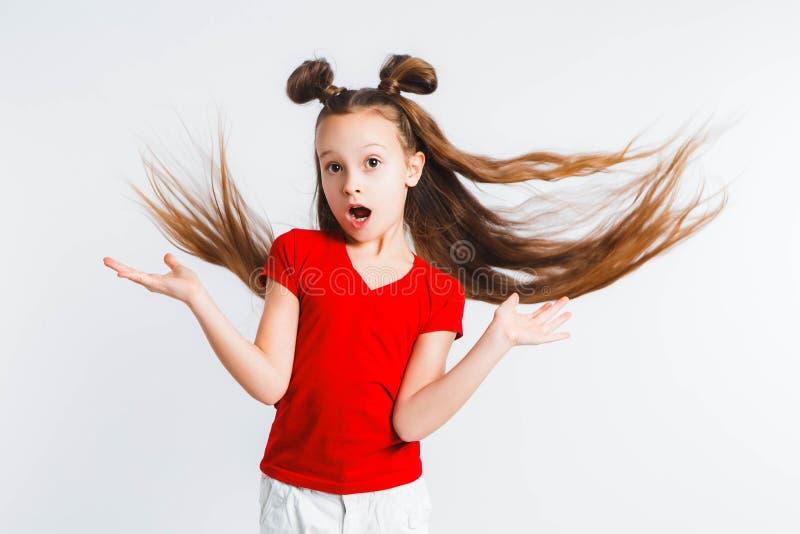 Meisjestiener met het vliegen haarschreeuwen en gebaren emotioneel Het voorstellen van uw product Expressieve gelaatsuitdrukkinge stock foto's