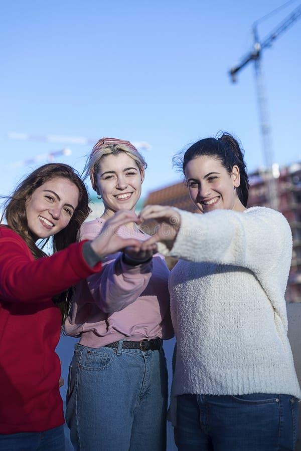 Meisjestieners in de zomer in het park in de verse lucht De gebaarhanden tonen het hart van liefde Gekleed in vrijetijdskleding royalty-vrije stock foto's