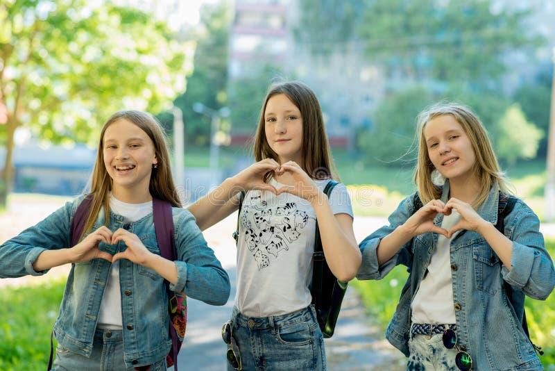 Meisjestieners in de zomer in het park in verse lucht De gebaarhanden tonen het hart van liefde Gekleed in vrijetijdskleding E royalty-vrije stock foto's