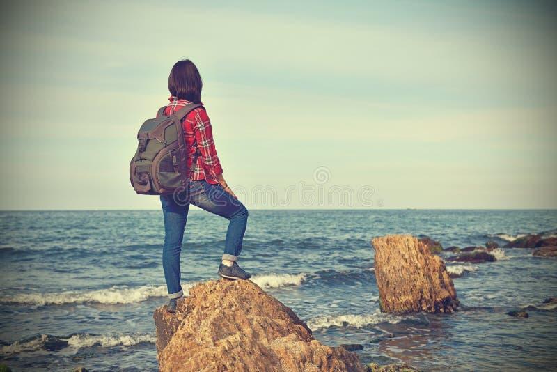 Meisjestoerist die zich op rots bevinden stock afbeeldingen