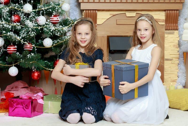 Meisjestweelingen met giftene Kerstboom stock foto's