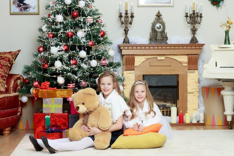 Meisjestweelingen met giftene Kerstboom royalty-vrije stock afbeelding