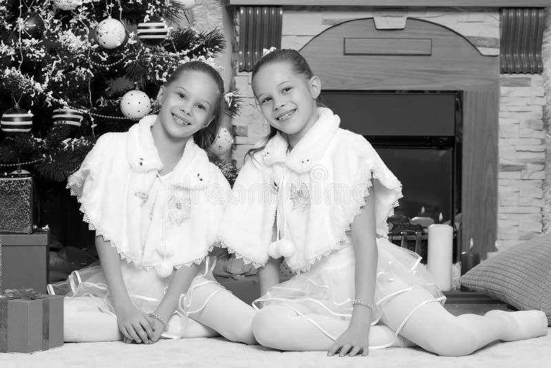 Meisjestweelingen met giftene Kerstboom stock afbeeldingen