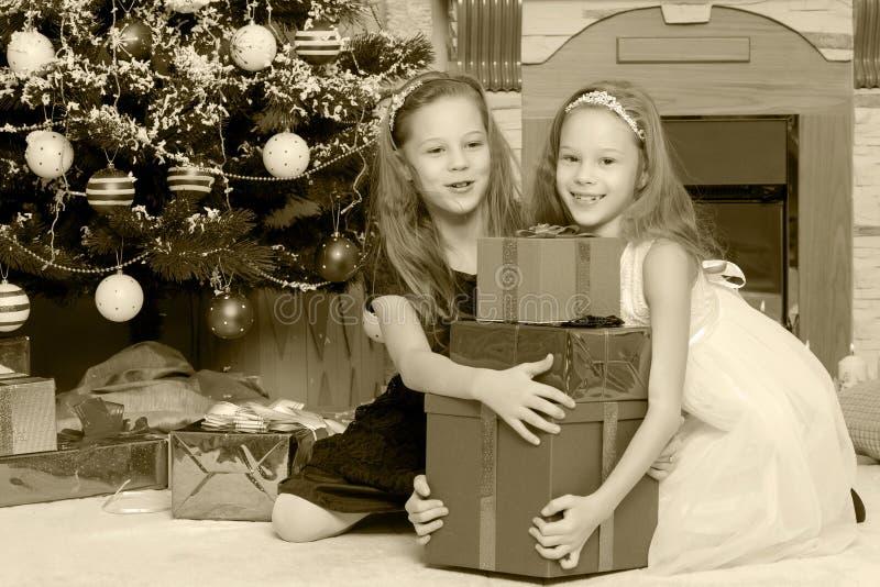 Meisjestweelingen met giftene Kerstboom stock afbeelding