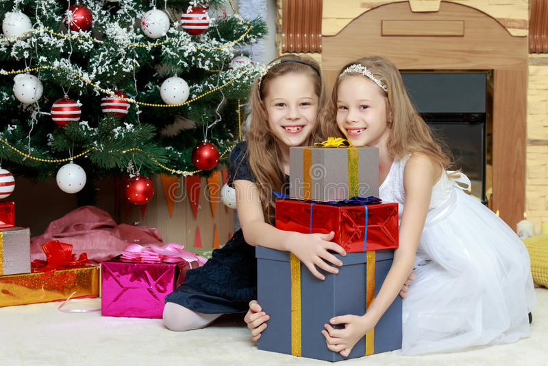 Meisjestweelingen met giftene Kerstboom royalty-vrije stock fotografie