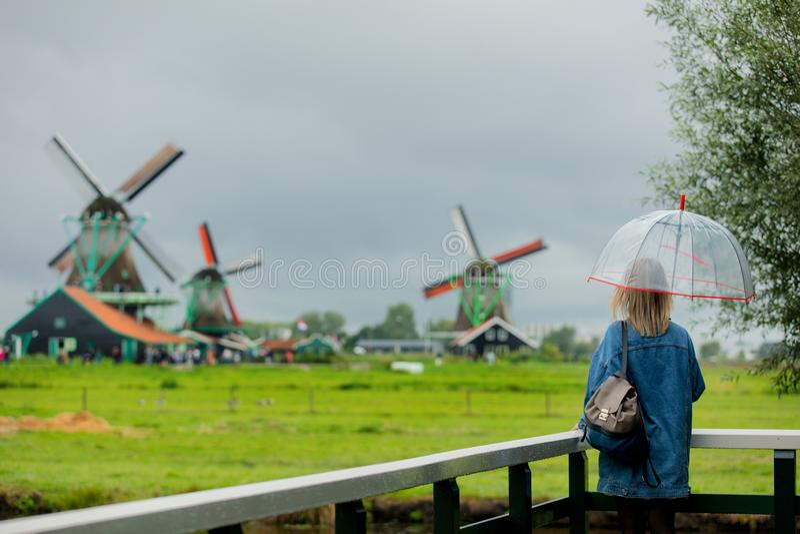 Meisjesverblijf op brug met Nederlandse molens royalty-vrije stock afbeeldingen