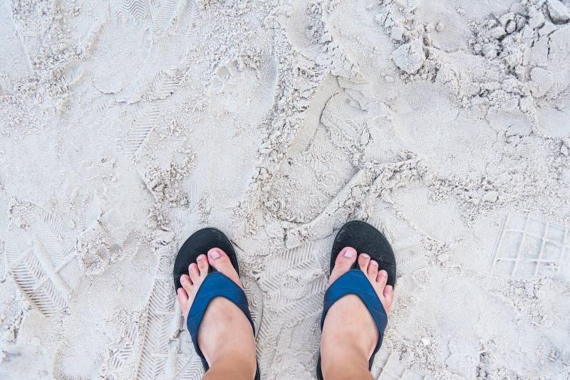 Meisjesvoeten in blauwe pantoffels op de textuur van het zandstrand Tropische kust kust thailand royalty-vrije stock fotografie