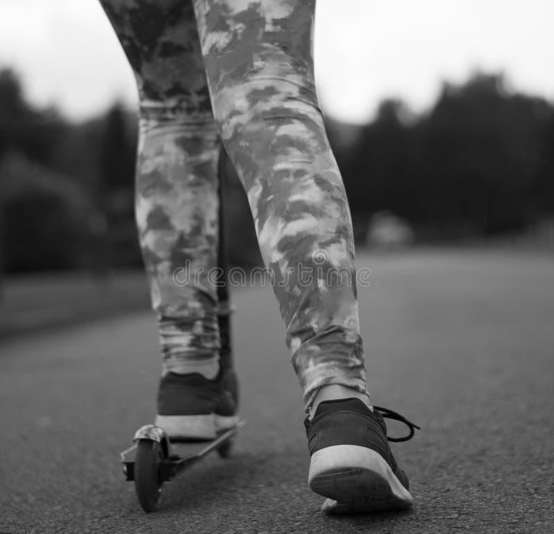 Meisjesvoeten, op autoped en andere het duwen weg van de weggrond royalty-vrije stock foto