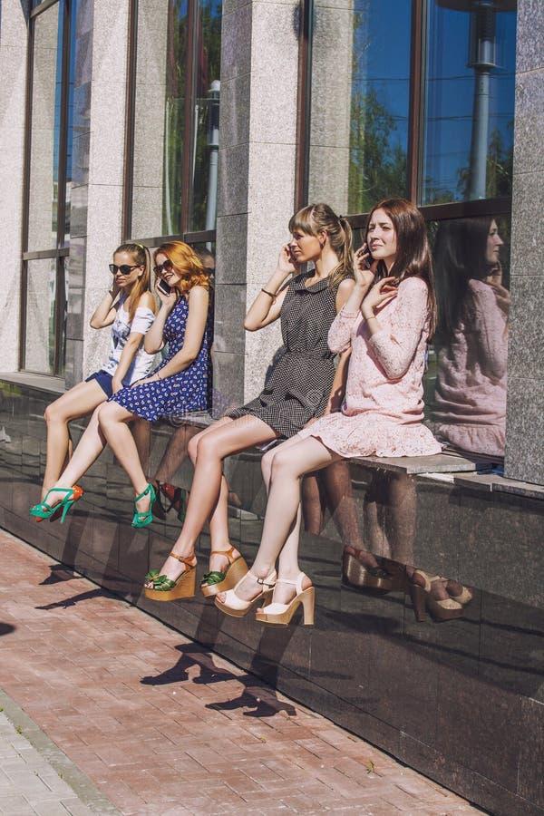 Meisjesvriend met een telefoongesprekzitting in de Vensters van een bouwstijl royalty-vrije stock foto's