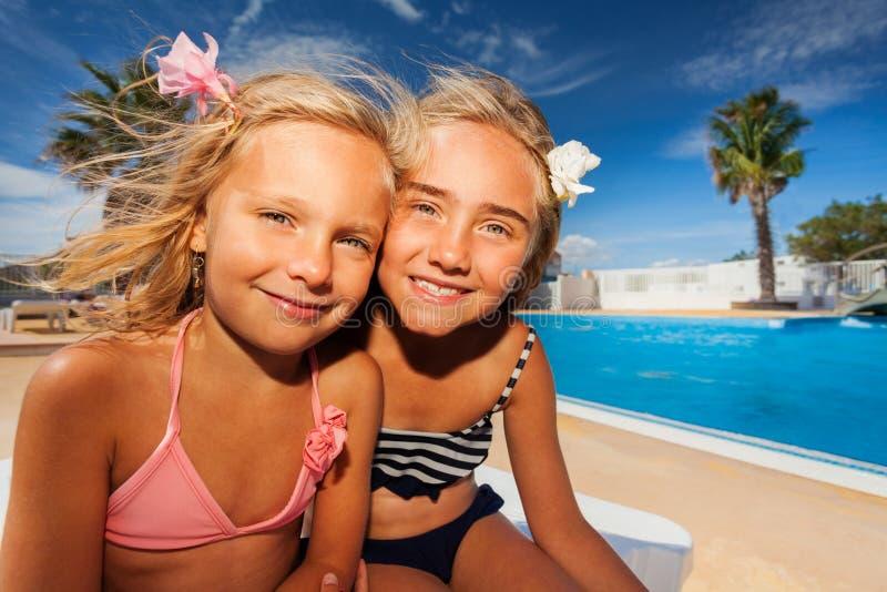 Meisjesvrienden die van de zomer genieten bij zwembad stock fotografie