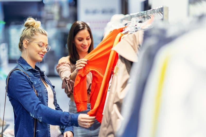 Meisjesvrienden die voor kleren in opslag winkelen stock foto