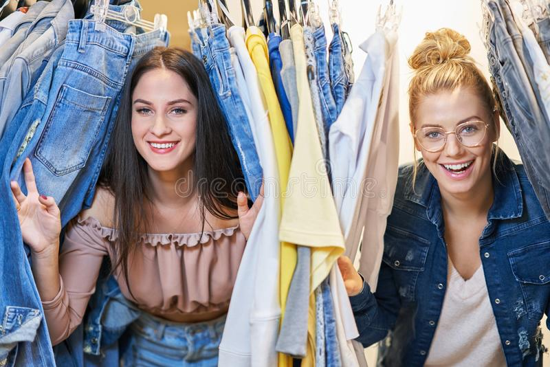 Meisjesvrienden die voor kleren in opslag winkelen stock fotografie