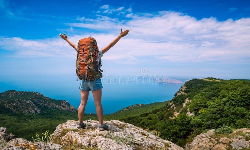 Meisjeswandelaar met opgeheven handen op een bergbovenkant royalty-vrije stock afbeeldingen