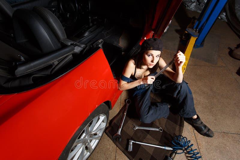 Meisjeswerktuigkundige in een garage stock foto