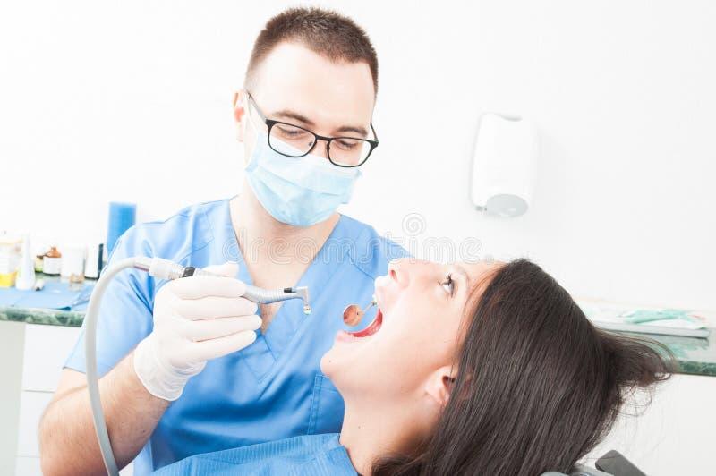 Meisjeszitting als tandartsvoorzitter die een procedure van arts hebben stock fotografie