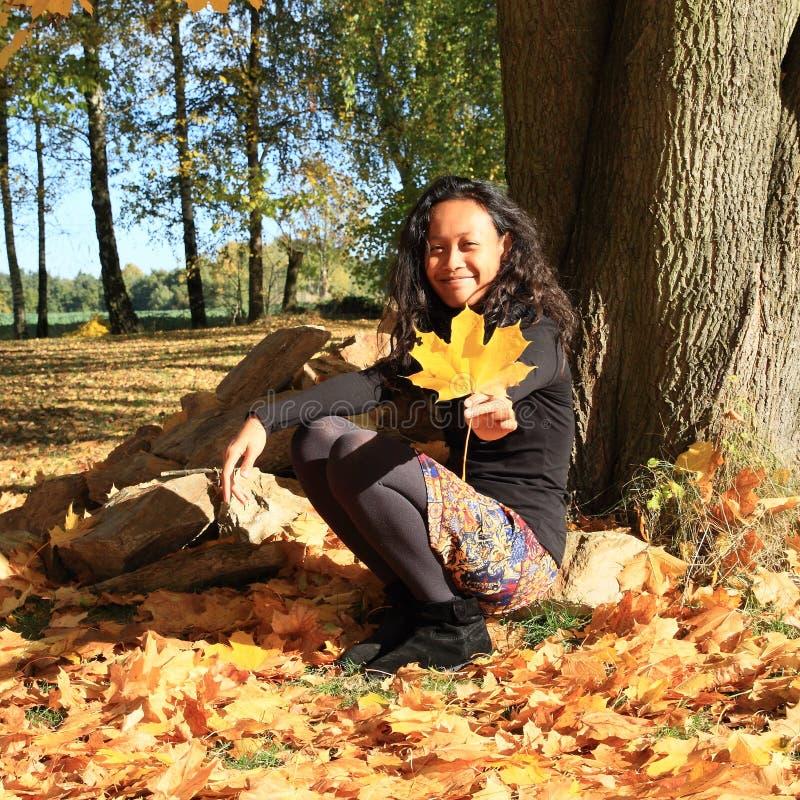 Meisjeszitting in gevallen bladeren royalty-vrije stock foto's