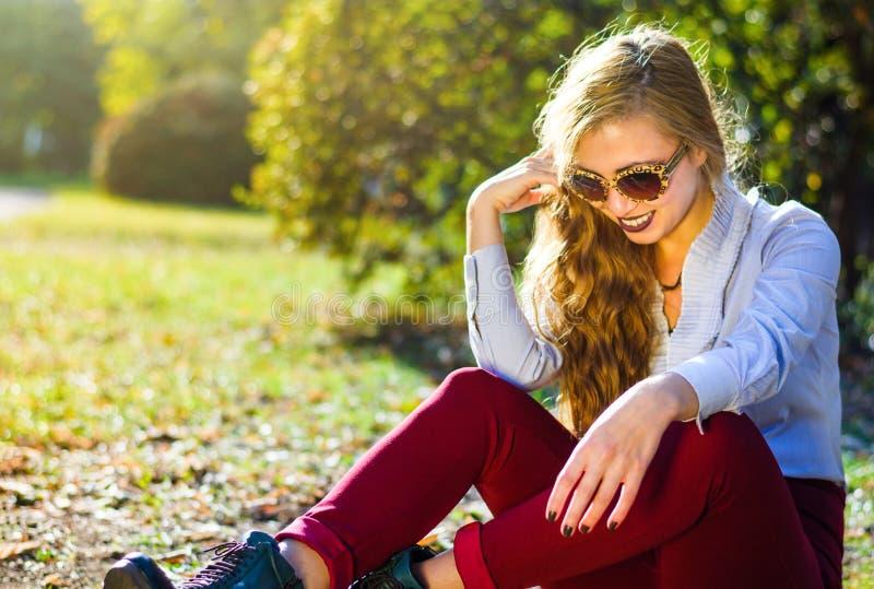Meisjeszitting in het park met de herfstbladeren dat wordt behandeld stock afbeeldingen