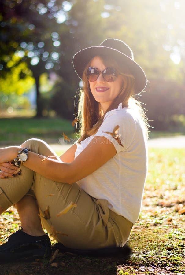 Meisjeszitting in het park met de herfstbladeren dat wordt behandeld stock foto's