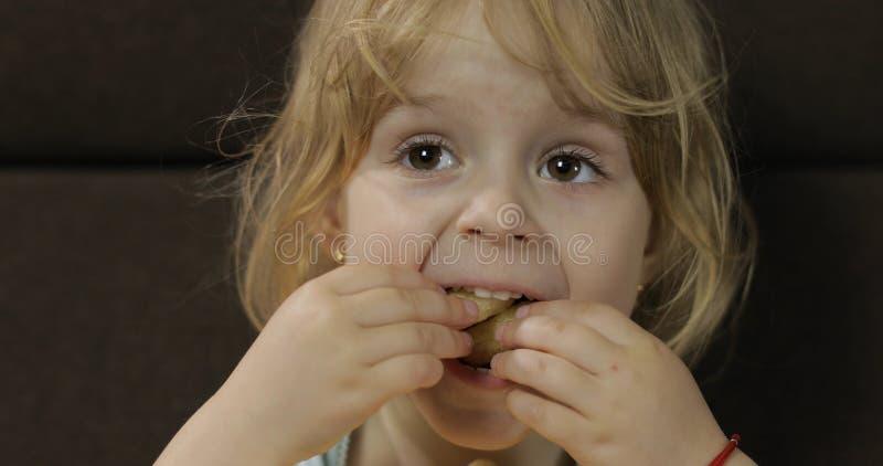 Meisjeszitting op bank en het eten van graanrookwolken Kindsmaak puffcorns royalty-vrije stock fotografie