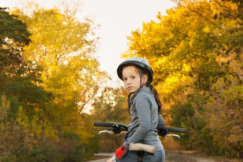 Meisjeszitting op de fiets Gang in de herfst Het berijden op de weg royalty-vrije stock afbeeldingen
