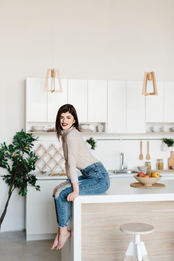 Meisjeszitting op de keukenlijst Heldere, witte keuken Gelukkig glimlachend meisje in de keuken Keuken royalty-vrije stock afbeelding