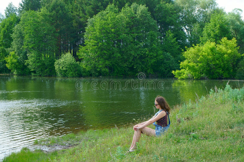 Meisjeszitting op de kust van meer royalty-vrije stock foto's