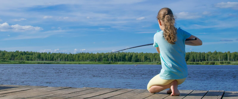 Meisjeszitting op de pijler en visserij, achtermening, tegen het meer stock fotografie