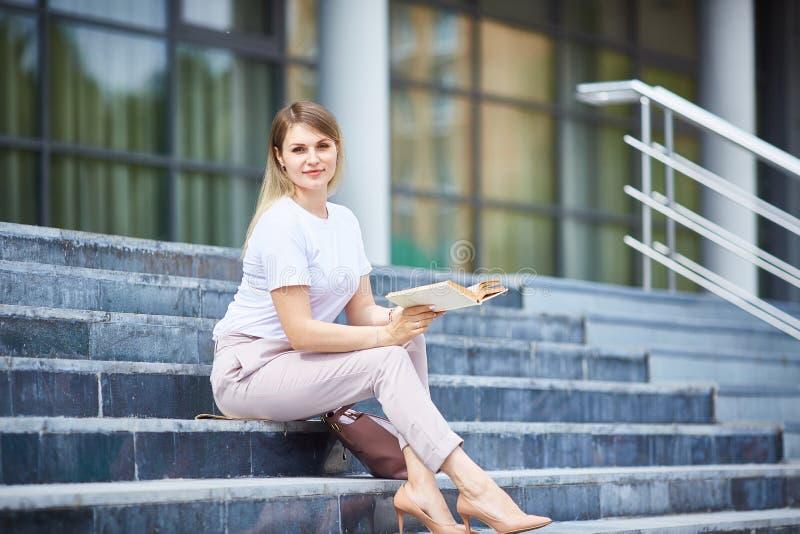 Meisjeszitting op de stappen die een boek lezen royalty-vrije stock afbeelding