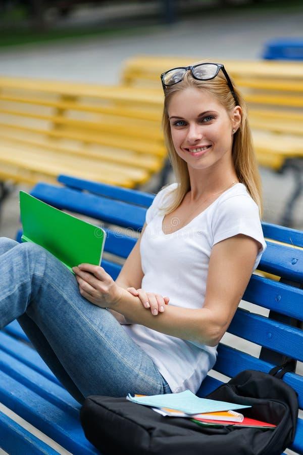 Meisjeszitting op de tablet van de bankholding stock fotografie