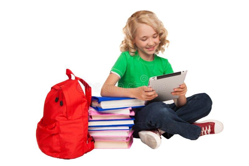 Meisjeszitting op de vloer dichtbij boeken en de tablet van de zakholding royalty-vrije stock afbeelding